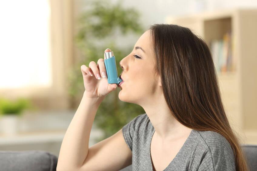 A young woman using an inhaler.