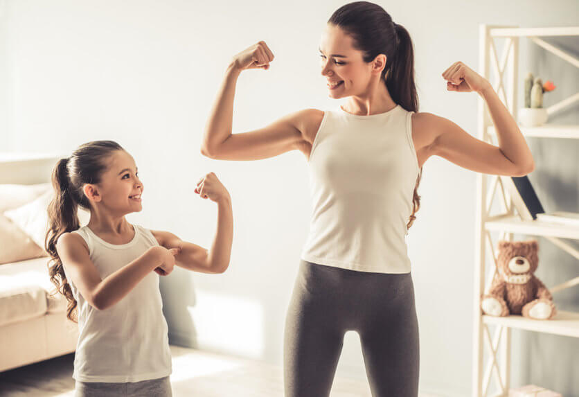 Mother and child flexing their muscles